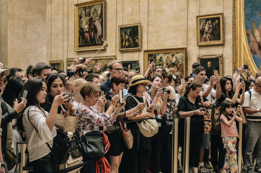 People standing in front of the Mona Lisa